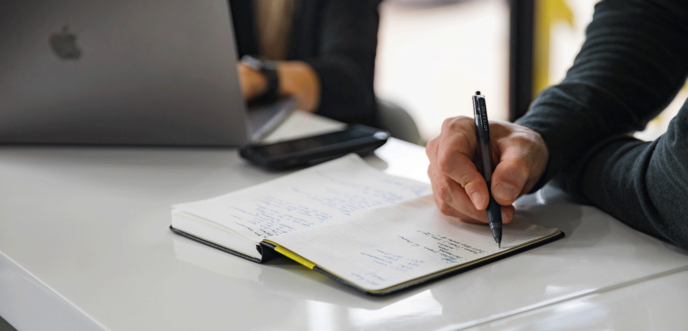 Man taking notes in notebook with black pen